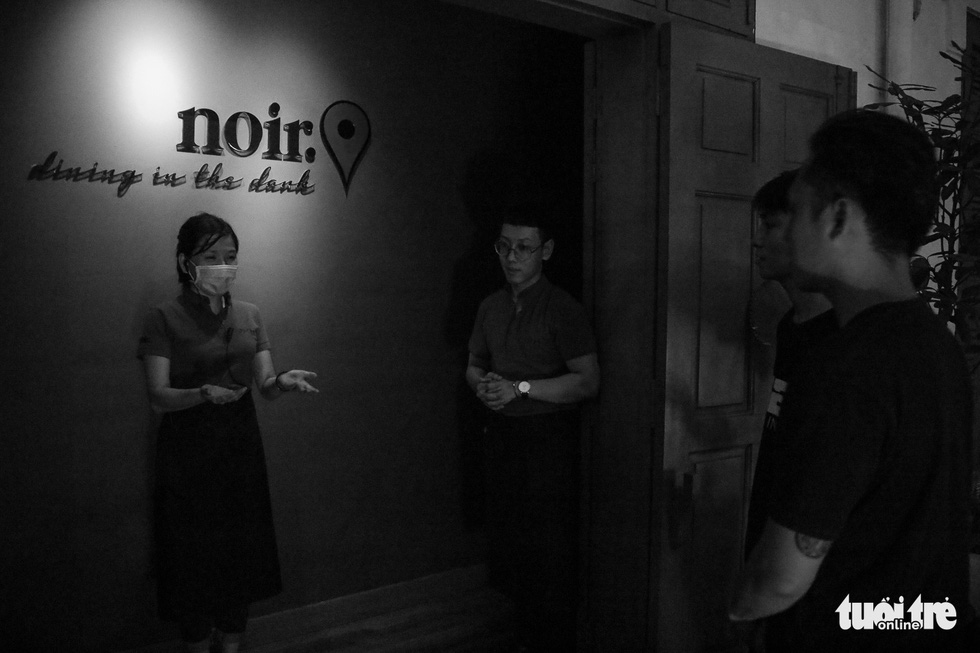 Trang (left), staff at Noir. Dining in the Dark restaurant on Hai Ba Trung Street in Ho Chi Minh City's District 1 introduces diners to the complete dark room at the venue. Photo: Ngoc Phuong/ Tuoi Tre