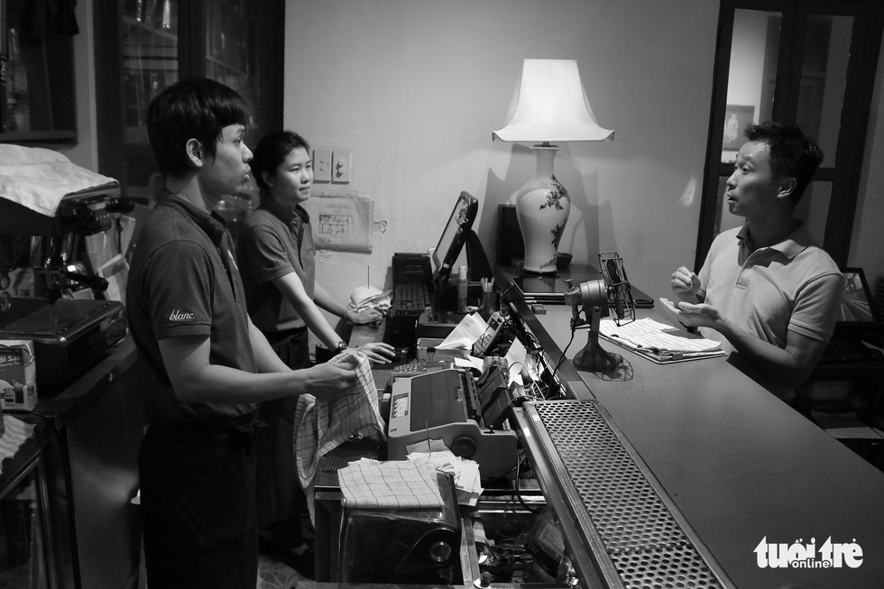 Vu Anh Tu (right), owner of the restaurant talks to his hearing impaired staff. Photo: Ngoc Phuong/ Tuoi Tre