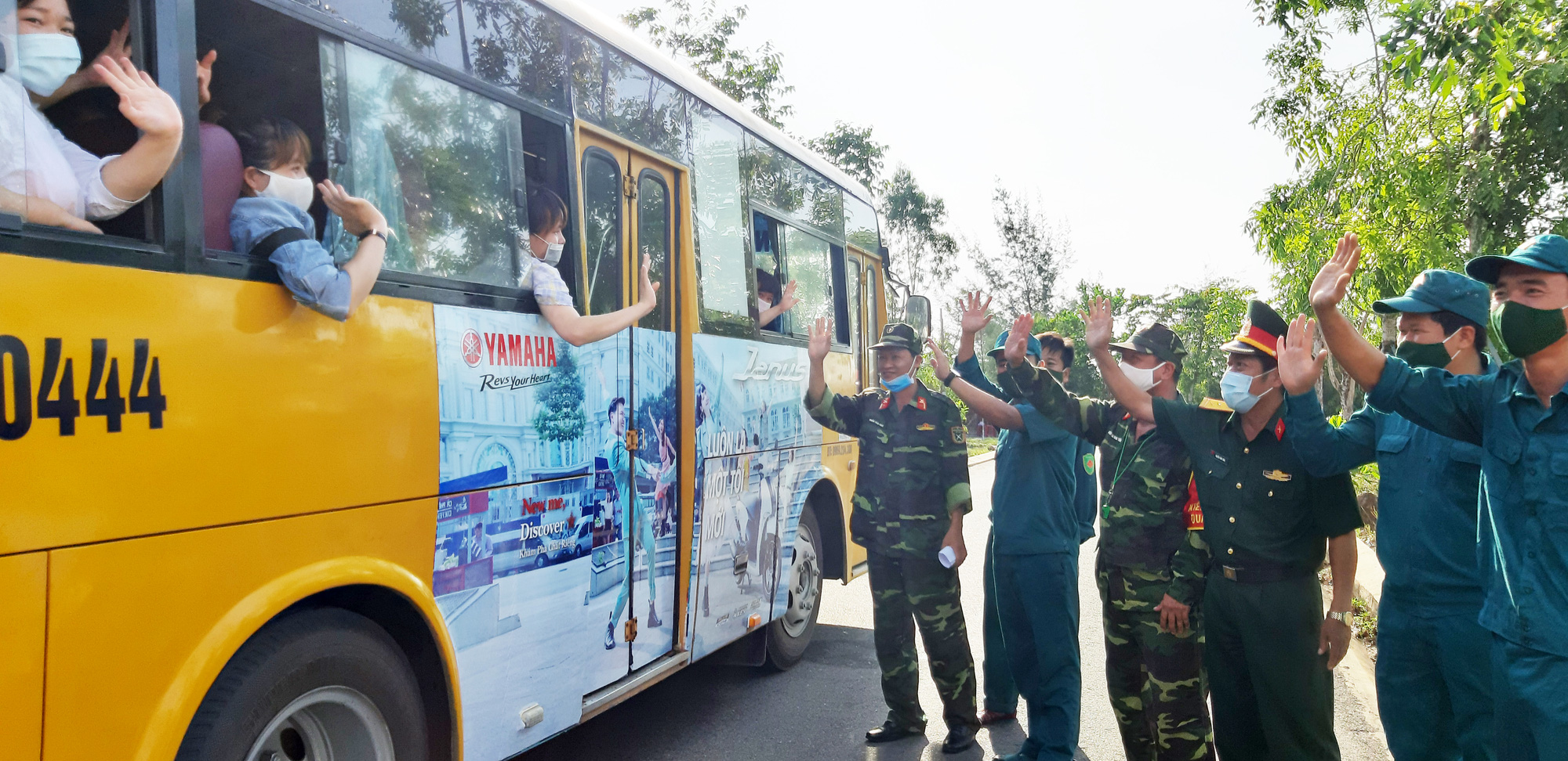 Residents wave goodbye to staff members and officers at a novel coronavirus disease (COVID-19) quarantine zone in Quang Nam Province, Vietnam from a bus before heading to the airport after completing their mandatory quarantine, June 12, 2020. Photo: Le Trung / Tuoi Tre