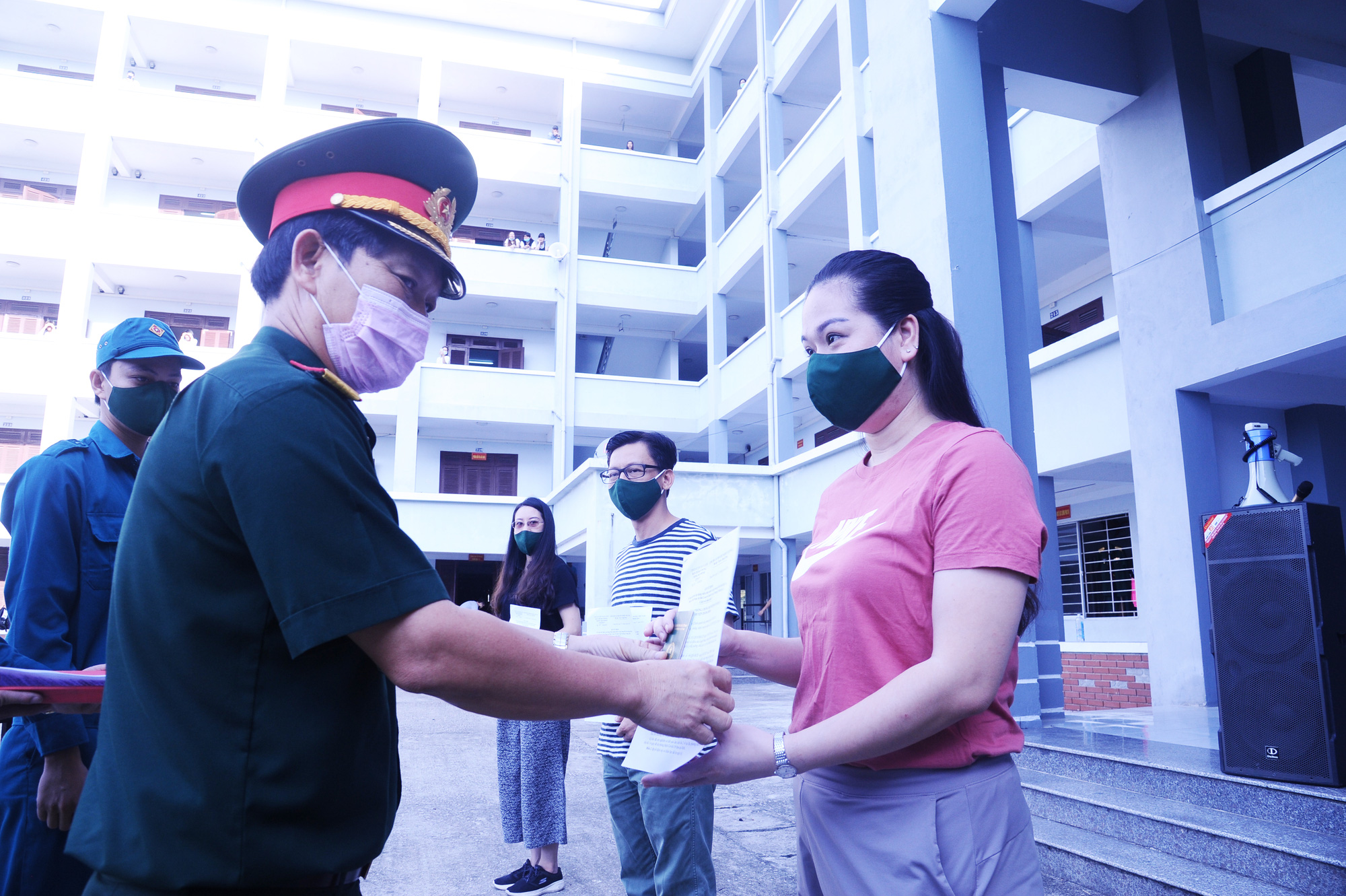 Col. Nguyen Huu Nghia (left) from Quang Nam Province's Military Command hands out all-clear certificates to residents at a novel coronavirus disease (COVID-19) quarantine facility in Quang Nam Province, Vietnam, June 12, 2020. Photo: Le Trung / Tuoi Tre