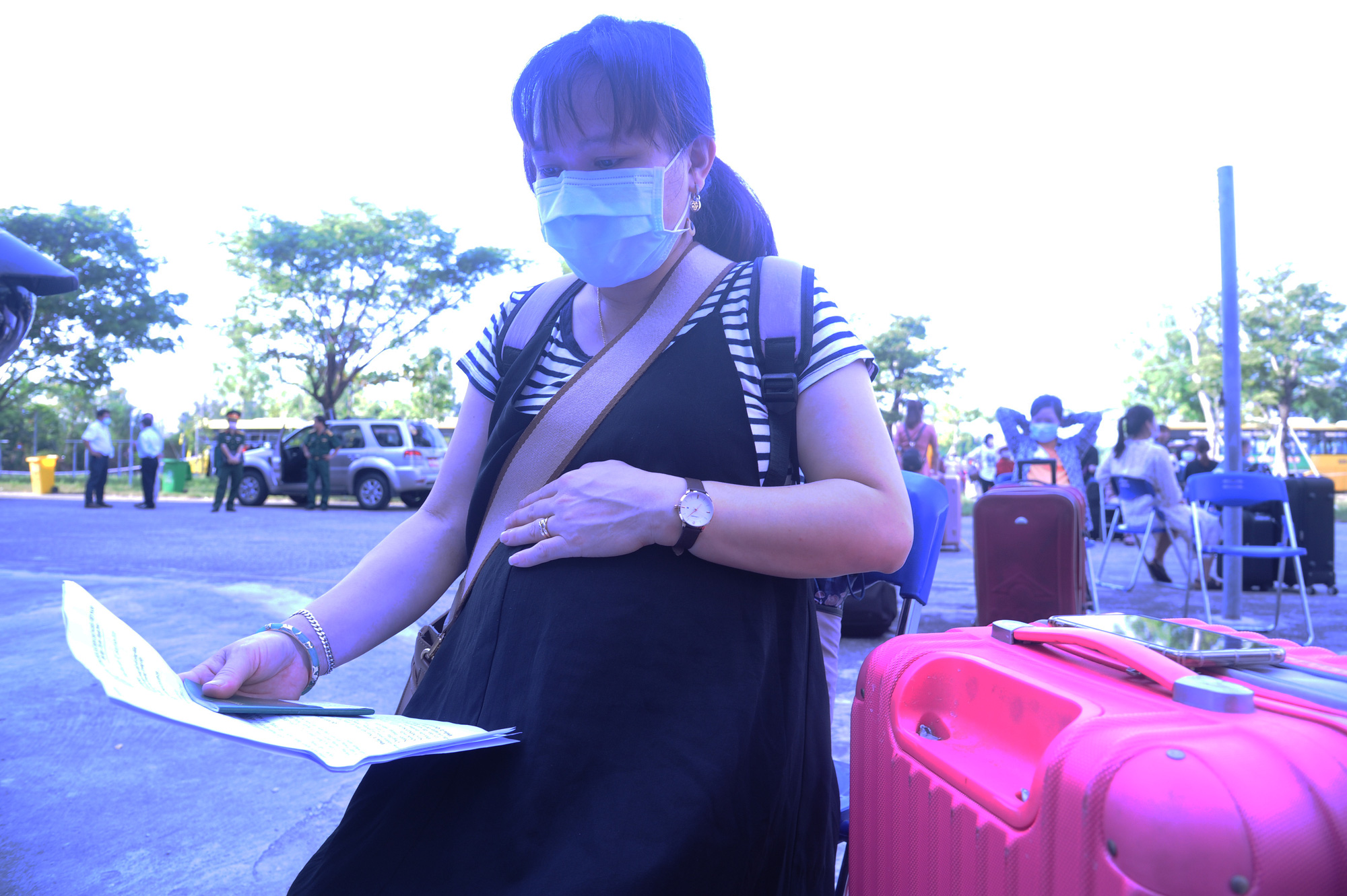 A pregnant woman holds her novel coronavirus disease (COVID-19) all-clear certificate after completing mandatory quarantine at a facility in Quang Nam Province, Vietnam, June 12, 2020. Photo: Le Trung / Tuoi Tre