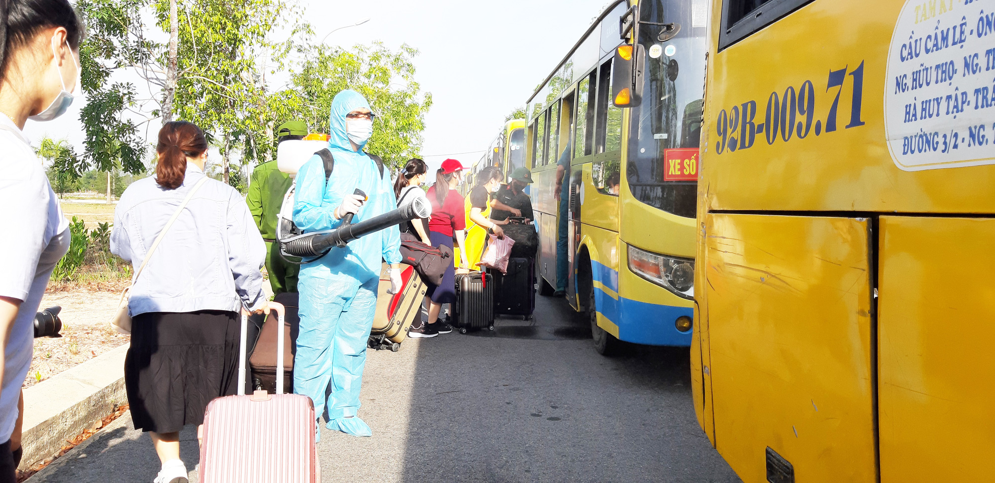 A medical worker disinfects buses used to transport residents at a novel coronavirus disease (COVID-19) quarantine zone in Quang Nam Province, Vietnam to the airport after they have completed their mandatory quarantine, June 12, 2020. Photo: Le Trung / Tuoi Tre