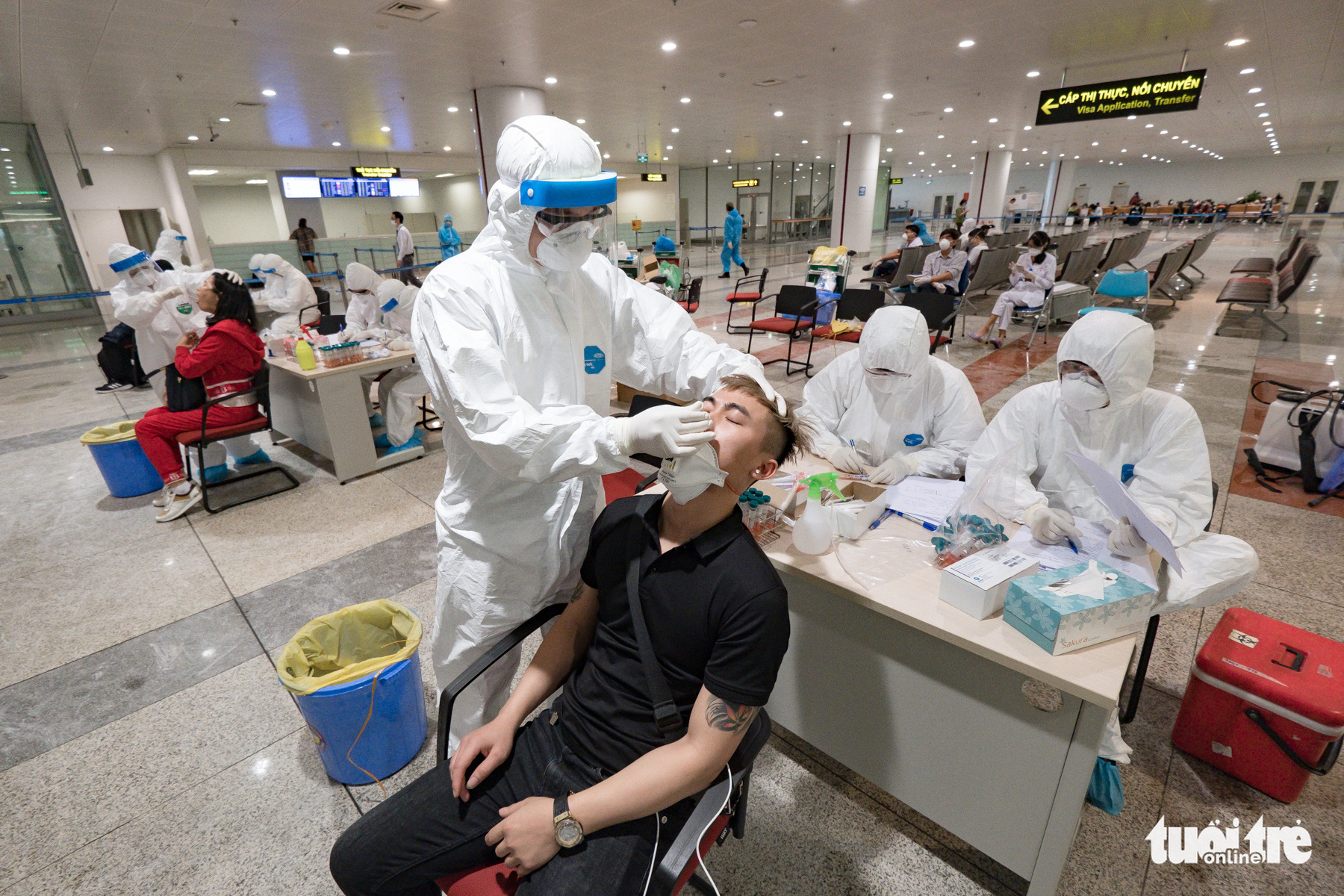 A health worker samples a man for novel coronavirus disease (COVID-19) testing at Noi Bai International Airport in Hanoi, Vietnam, March 18, 2020. Photo: Nam Tran / Tuoi Tre