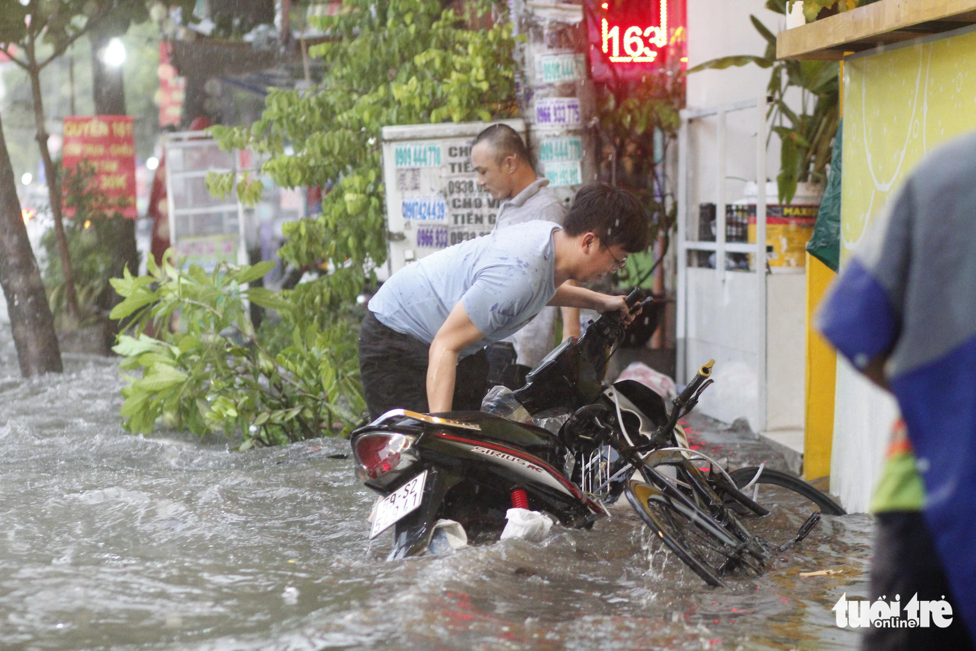 A man struggles to push his motorbike on a flooded street in Ho Chi Minh City, June 16, 2020. Photo: Chau Tuan / Tuoi Tre