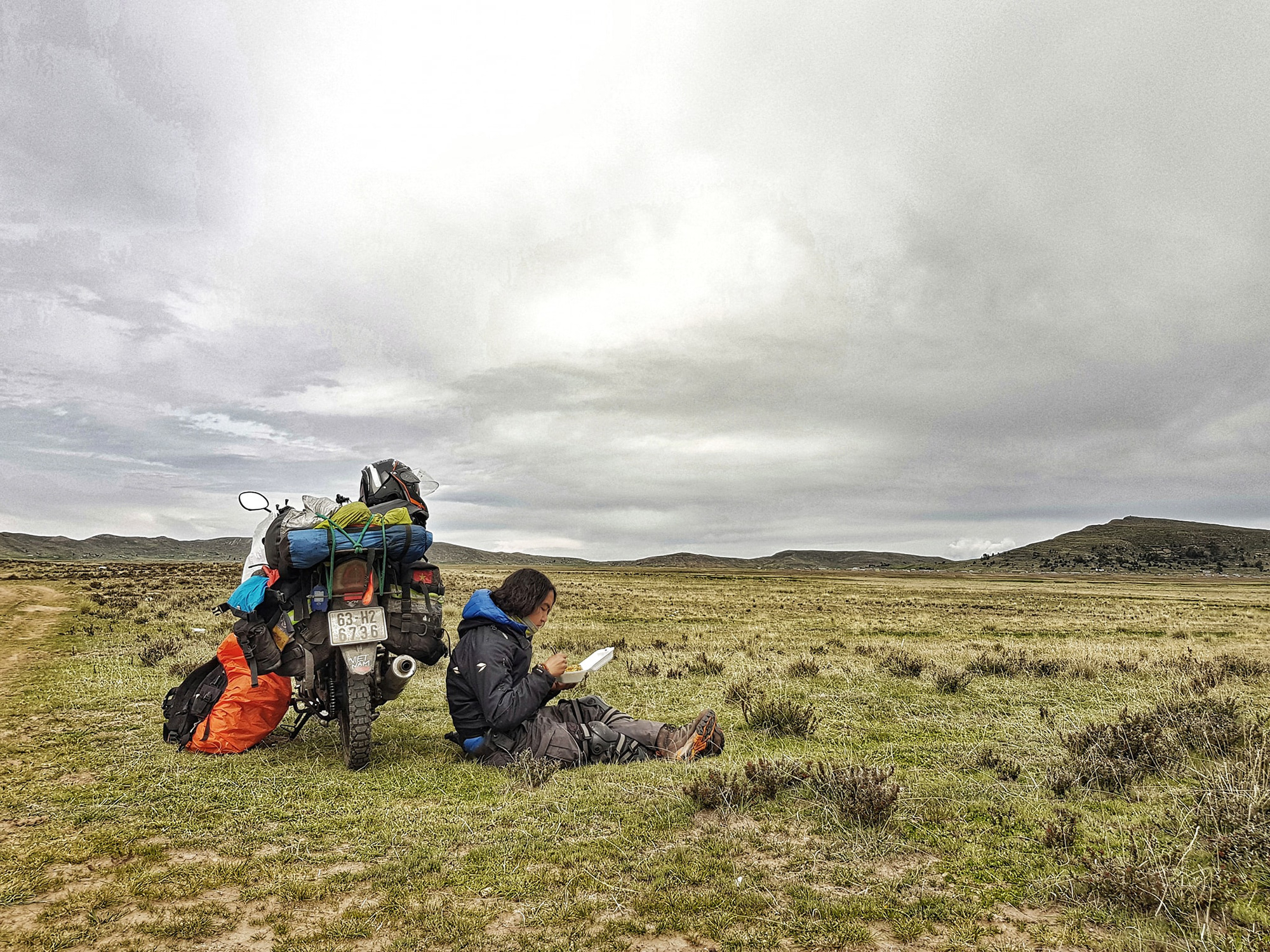 Vietnamese globetrotter Tran Dang Dang Khoa takes a break, sitting beside his bike to have lunch in an open field during his journey around the world in a photo posted to his verified Facebook account.