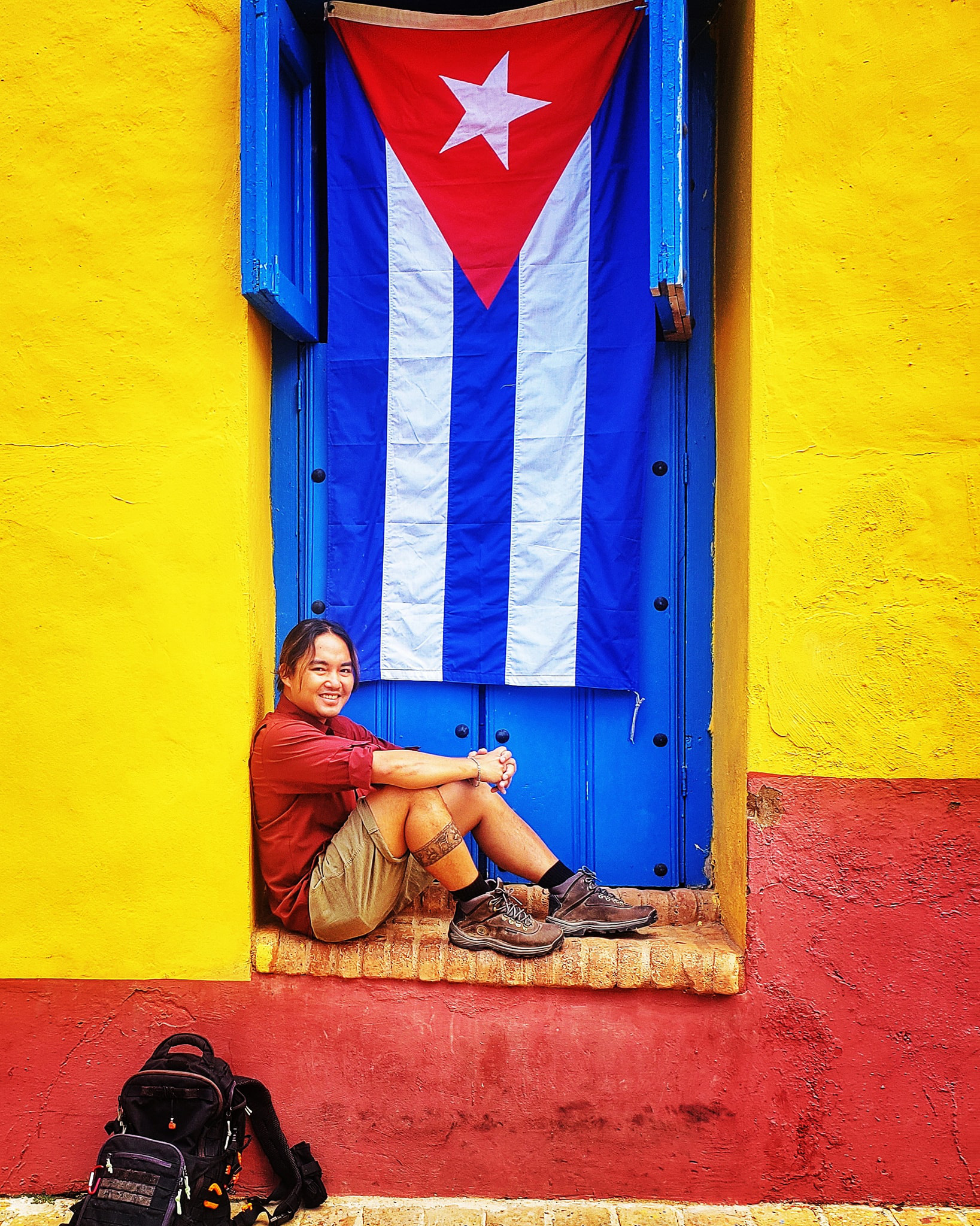 Vietnamese globetrotter Tran Dang Dang Khoa poses for a photo against the backdrop of a Cuban flag in Cuba in a photo posted to his verified Facebook account.