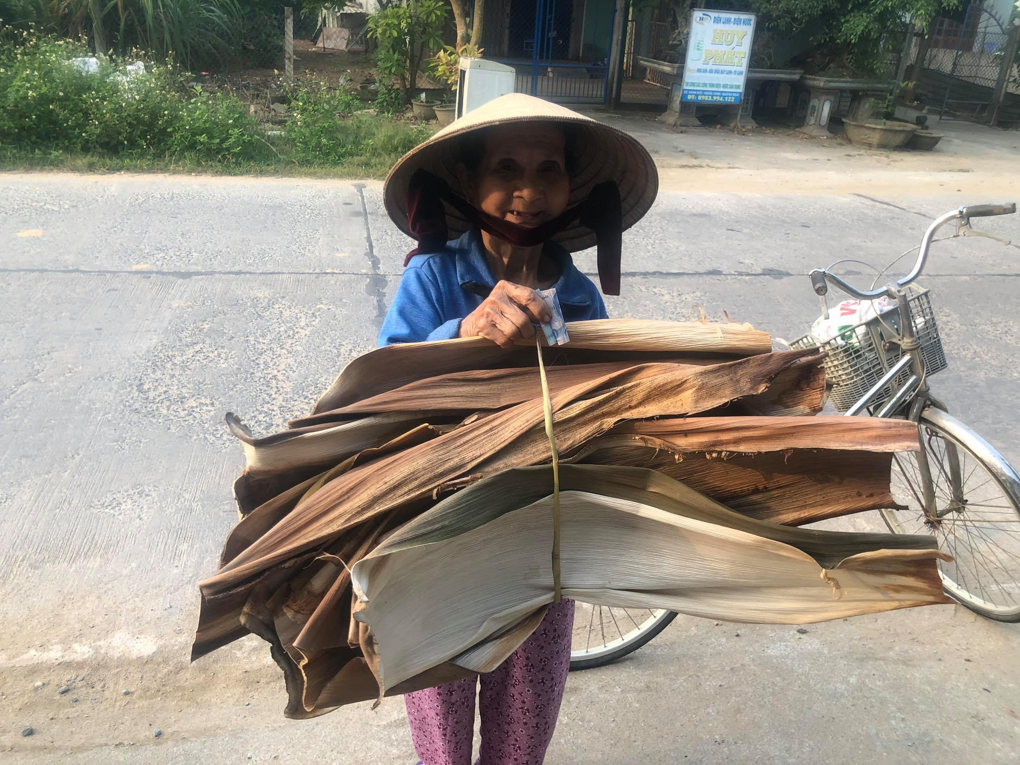 Tran Thi Mai from Phu Chau Village, Hanh Duc commune, Nghia Hanh District, Quang Ngai Province rides a bicycle delivering areca leaves to Nguyen Van Tuyen's factory, which makes tableware from the agricultural by-product. Photo: Lam Minh Khoa