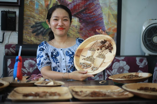 Artist Nguyen Thi Dieu Hien and an artwork made from areca leaves are seen in this photo on Facebook.