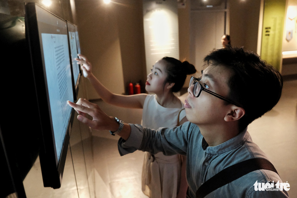Two guests use a touch screen to look up exhibits at the Vietnam Press Museum in Hanoi in this undated photo. Photo: Mai Thuong / Tuoi Tre