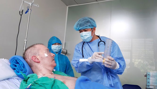 Dr. Tran Thanh Linh (right), deputy head of the intensive care unit at Cho Ray Hospital in Ho Chi Minh City, shows a British man who is Vietnam's novel coronavirus disease (COVID-19) patient No. 91 how to use a breathing exercise equipment during his treatment at the infirmary, June 17, 2020. Photo: Duyen Phan / Tuoi Tre