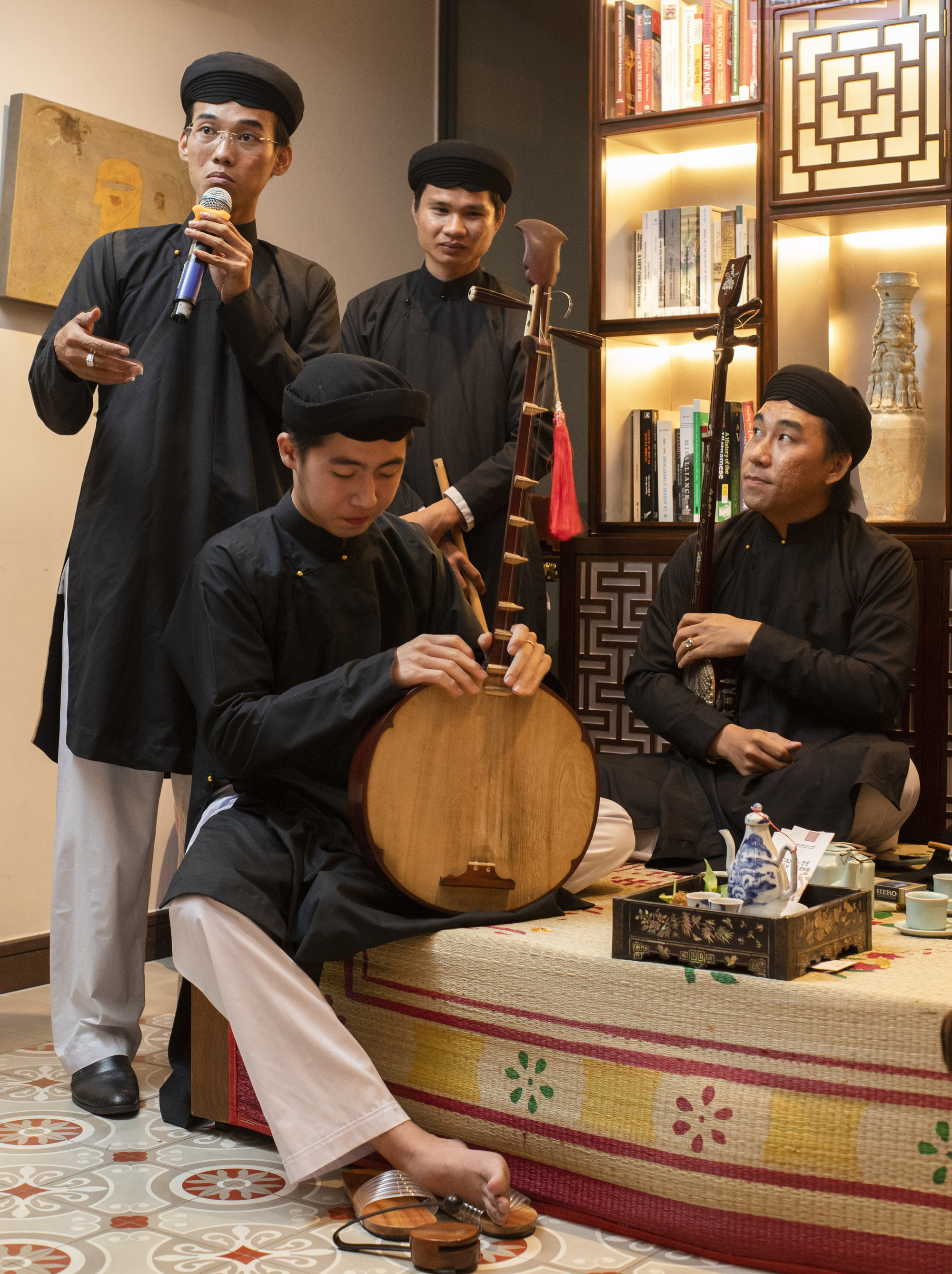 Dai Nam Club members in traditional clothes discuss Vietnamese musical instruments during a cultural event in a supplied photo.