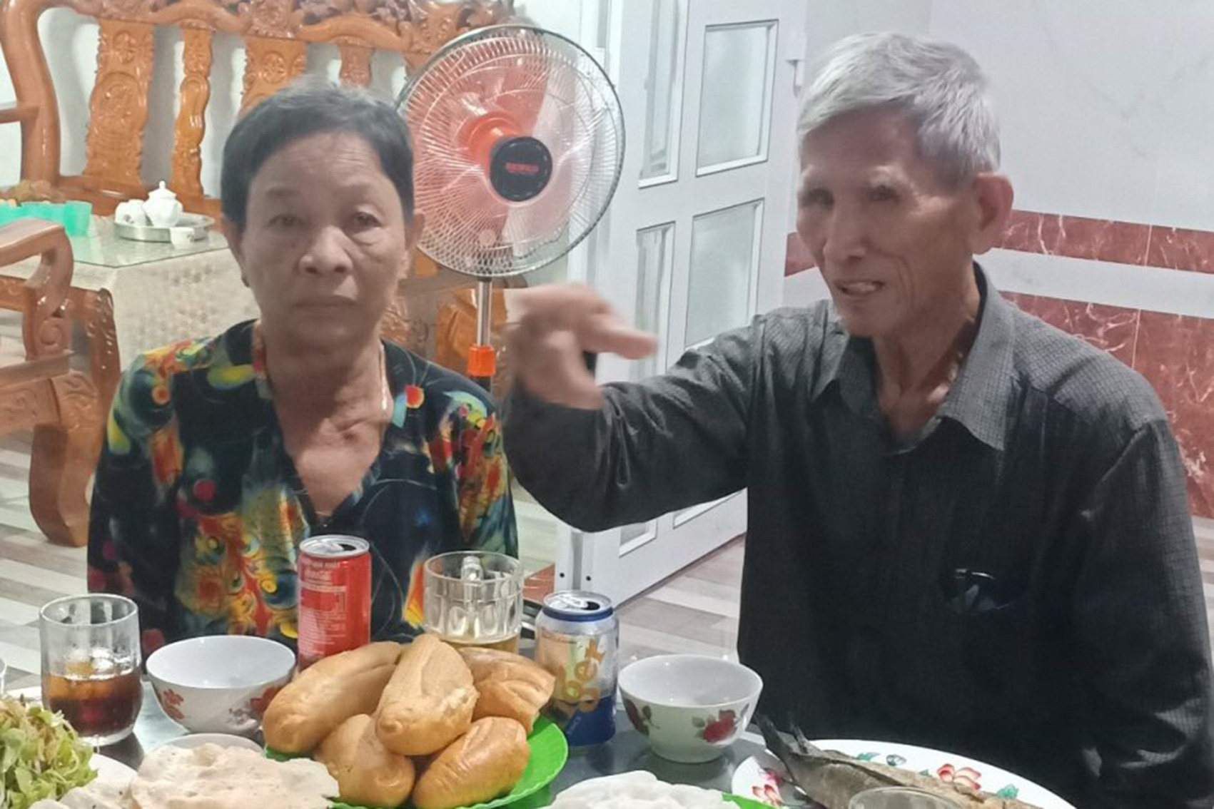 Pham Thi Sau (left) and her brother Pham Sung sit in a meal after being separated for 50 years in this photo supplied by the family.