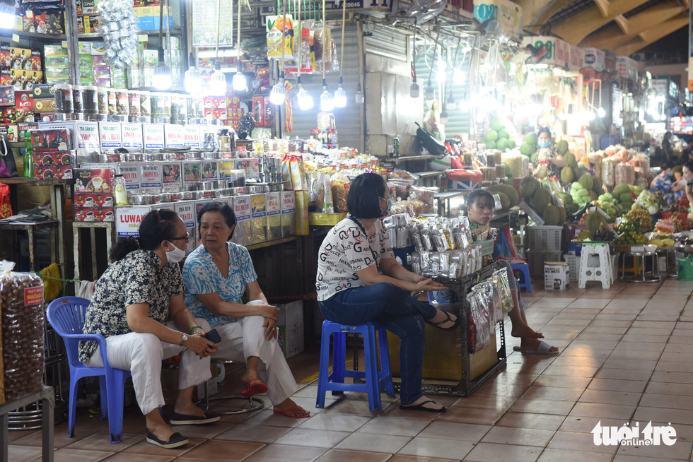 Sellers chit chat to kill time as Ben Thanh Market has received almost no foreign tourists, the place's major customers, for months due to COVID-19. Photo: Duyen Phan/ Tuoi Tre
