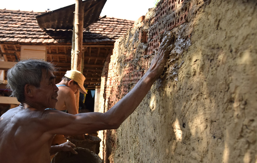 Builders fill holes in the bricks around the kiln wall with wet clay. Photo: Le Van Anh / Tuoi Tre