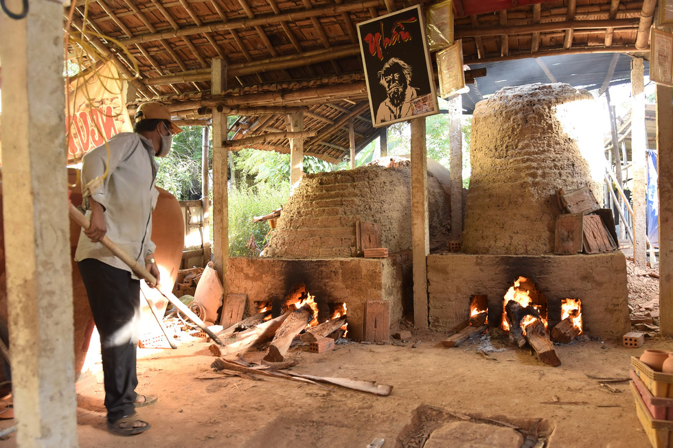 A ceramic worker adjusts the fire temperature in the kiln. Photo: Le Van Anh / Tuoi Tre