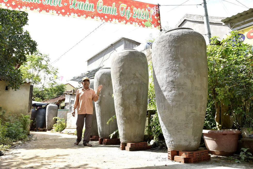 Artisan Nguyen Van Chin stands next to his giant pots. Photo: Le Van Anh / Tuoi Tre