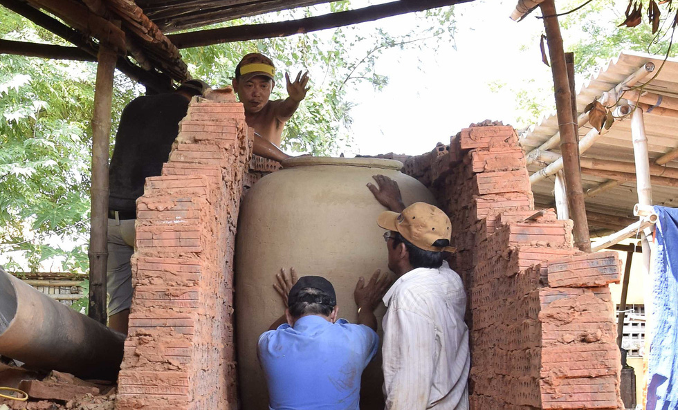 Ceramic workers put a piece of pottery in the kiln. Photo: Le Van Anh / Tuoi Tre