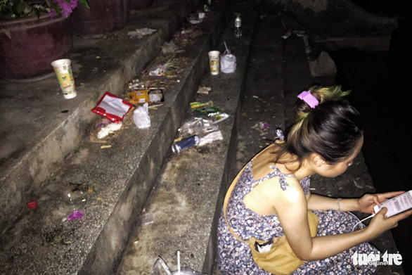 A woman sits next to trash on the steps in a lakeside neighborhood of an emerging Instagrammable spot down Alley 5 on Tu Hoa Street in Hanoi's Tay Ho District. Photo: Song La/ Tuoi Tre