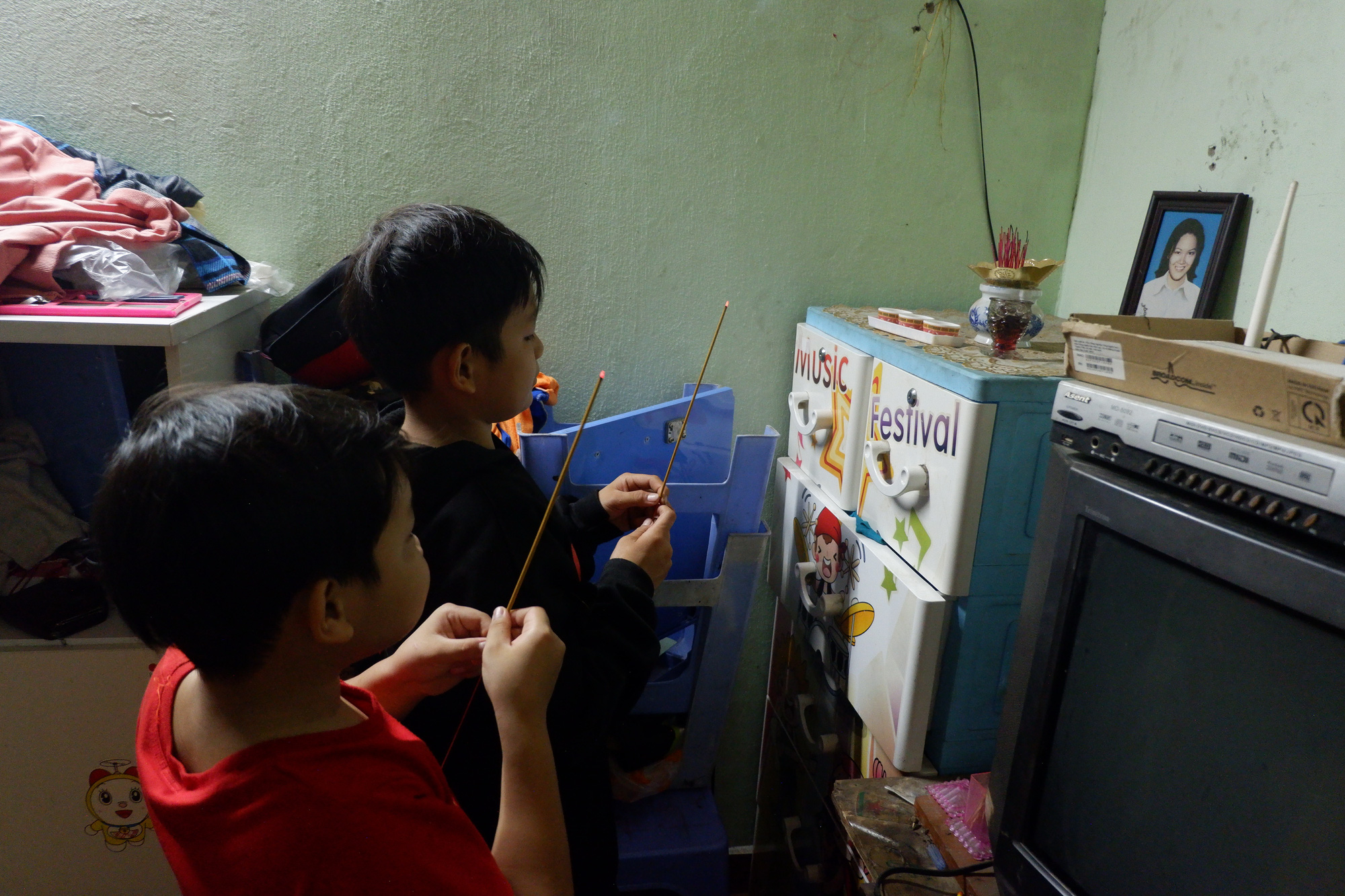 Ho Thi Ngoc's adoptive sons offers incense to their biological mother at their rented room in Long An Province in Vietnam's Mekong Delta. Photo: Son Lam / Tuoi Tre