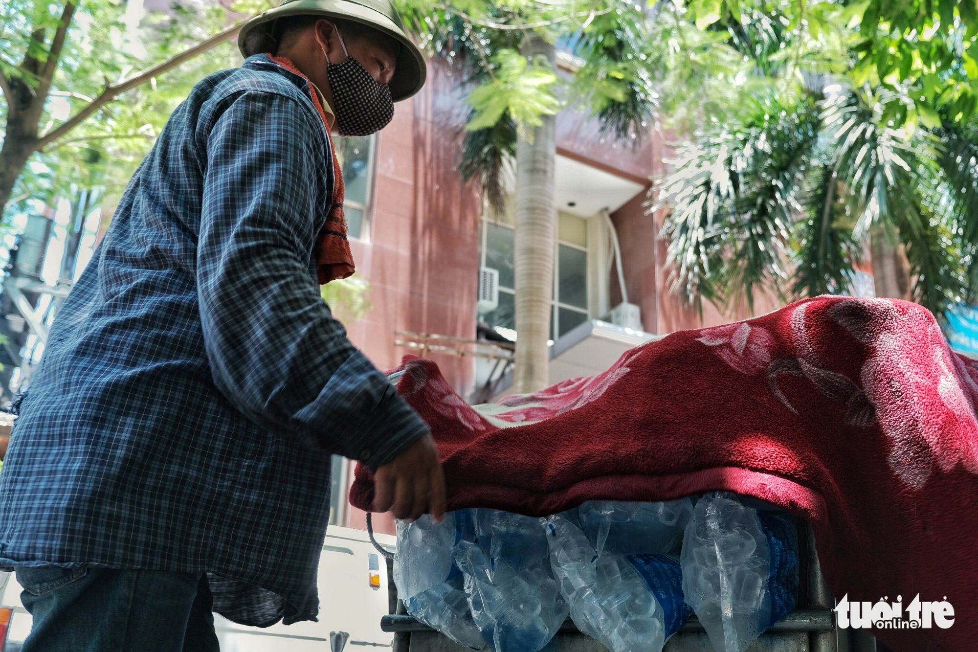 A delivery man covers ice packs with a blanket to keep them from melting in Hanoi, June 23, 2020. Photo: Mai Thuong / Tuoi Tre