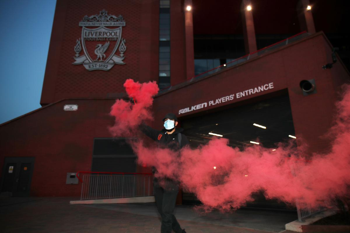 A Liverpool fan celebrates with a flare outside Anfield after Chelsea scored their second goal in their match against Manchester City, Liverpool, Britain, June 25, 2020. Photo: Reuters