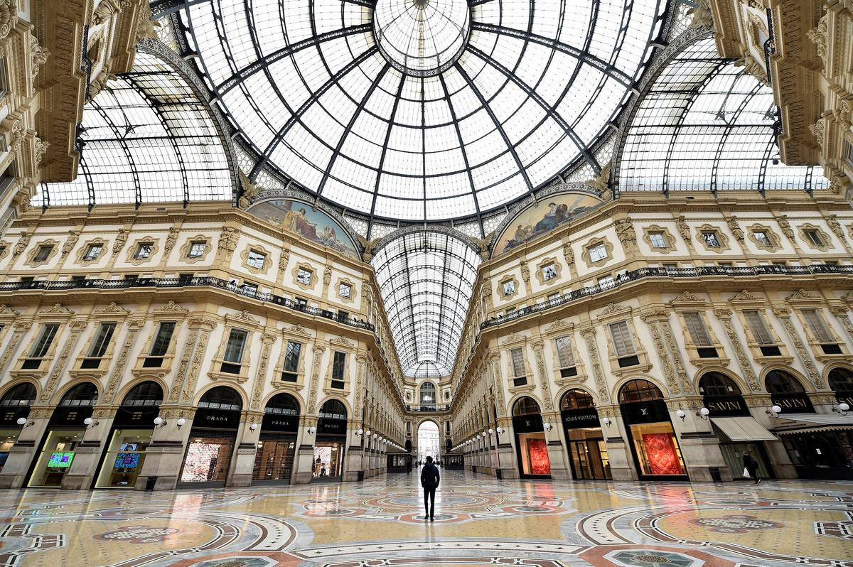 A person stands inside a deserted Galleria Vittorio Emanuele II, on the third day of an unprecedented lockdown across of all Italy imposed to slow the outbreak of coronavirus, in Milan, Italy, March 12, 2020. Photo: Reuters