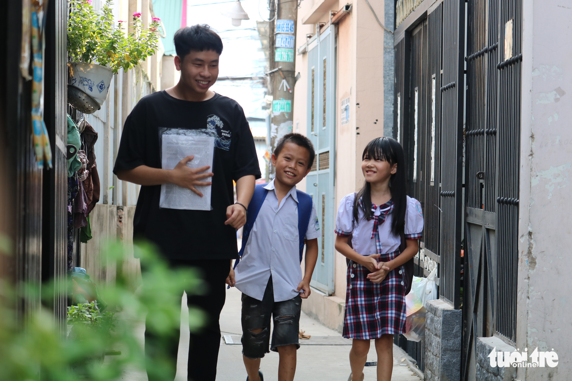 Phan Trung Hai (left) walks with his students on the way to his class for underprivileged kids in Ho Chi Minh City, Vietnam. Photo: Ngoc Phuong / Tuoi Tre