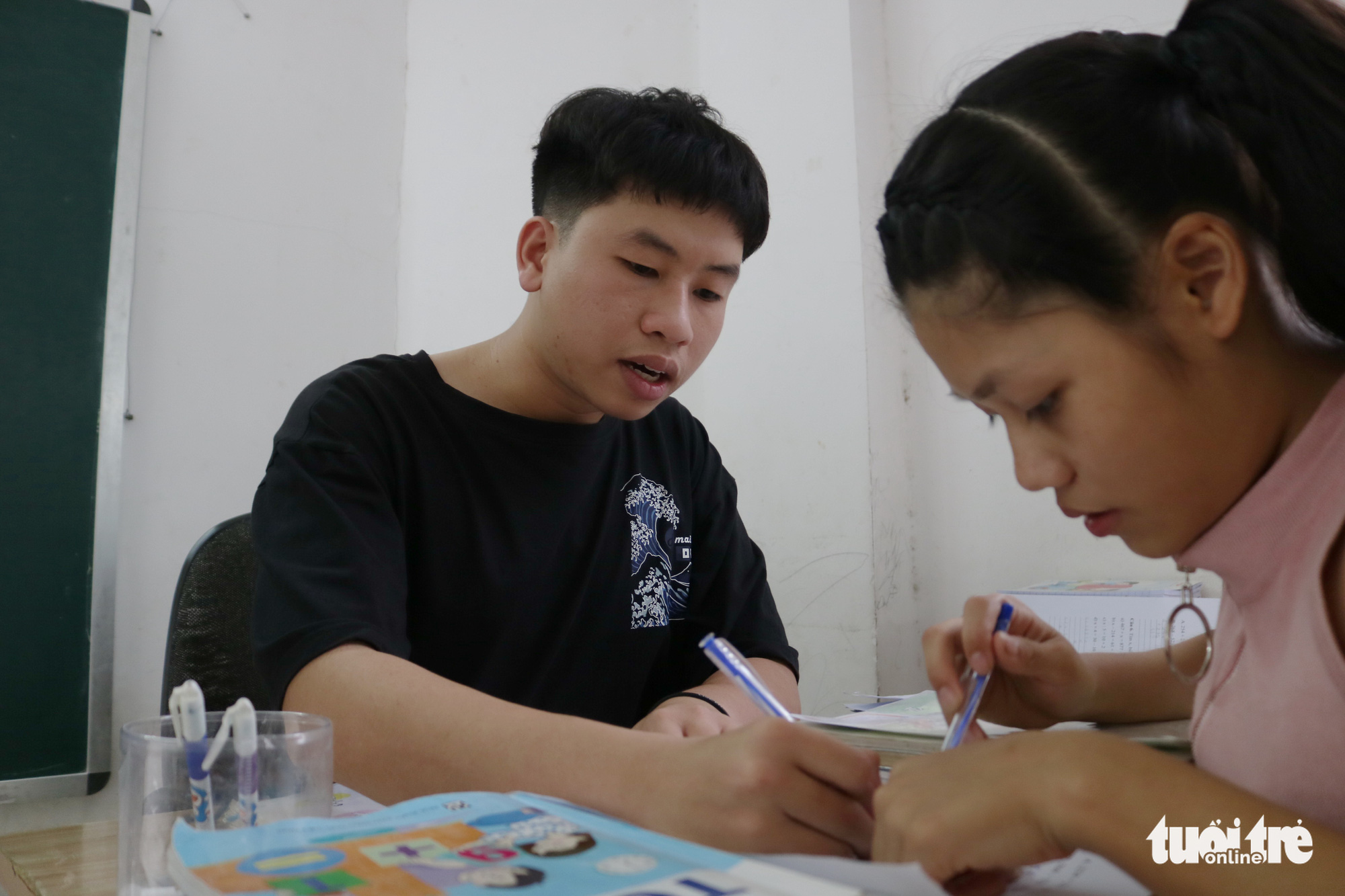 Phan Trung Hai guides a student to solve a problem in this special class for underprivileged children in Ho Chi Minh City, Vietnam. Photo: Ngoc Phuong / Tuoi Tre
