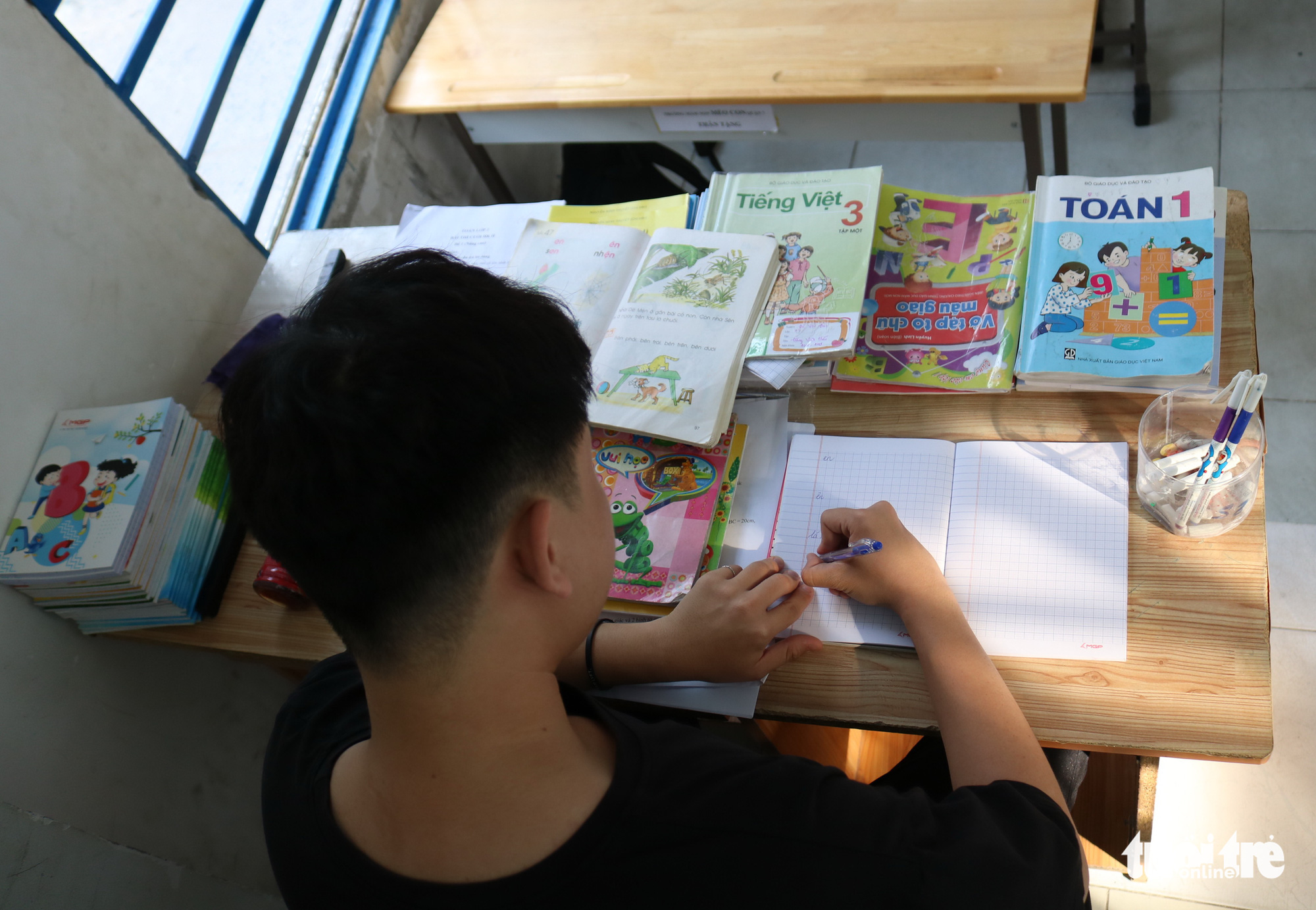 Phan Trung Hai works in the teacher's seat in this special class for underprivileged children in Ho Chi Minh City, Vietnam. Photo: Ngoc Phuong / Tuoi Tre
