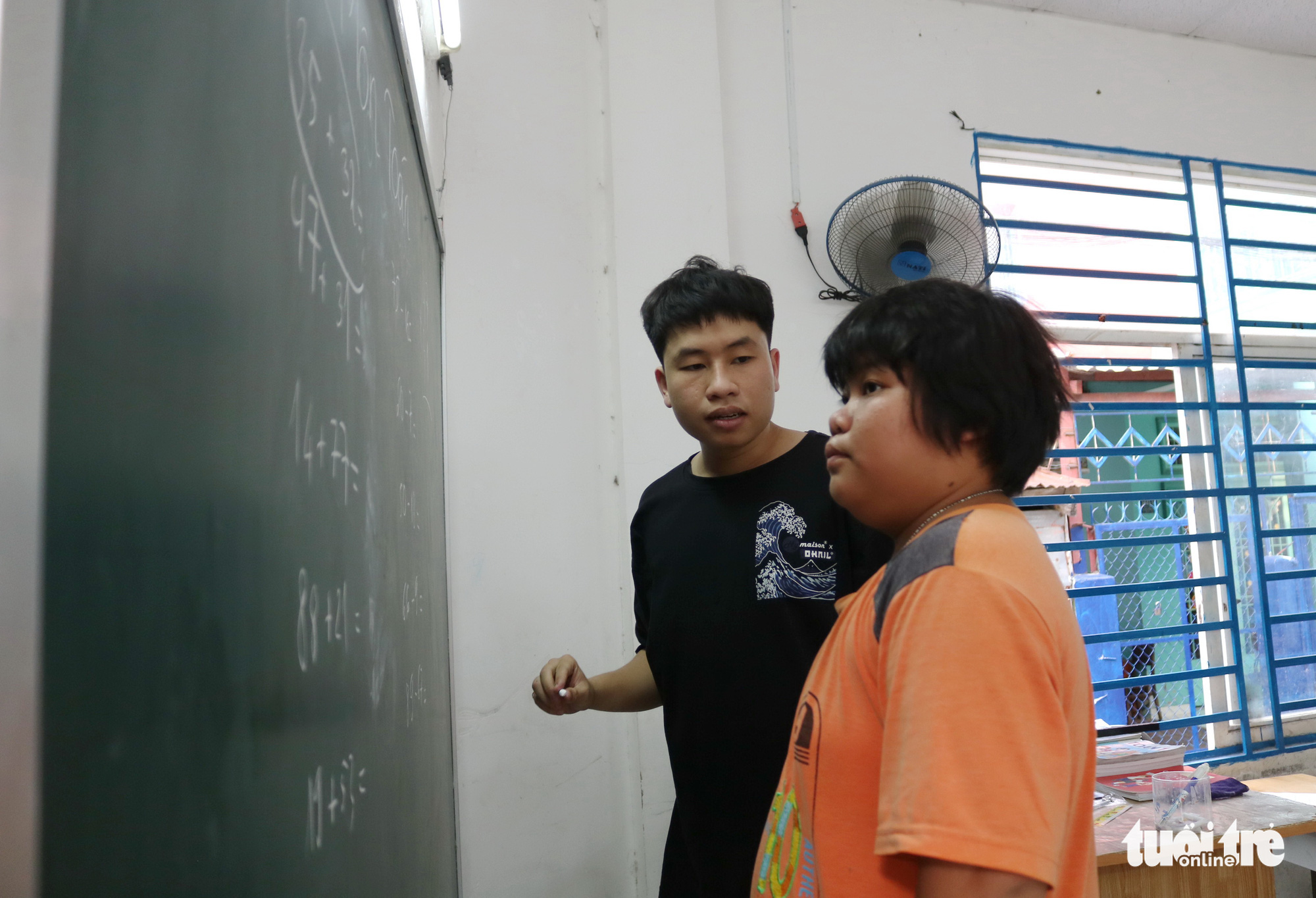 Phan Trung Hai helps a student solve math problems in this special class for underprivileged children in Ho Chi Minh City, Vietnam. Photo: Ngoc Phuong / Tuoi Tre
