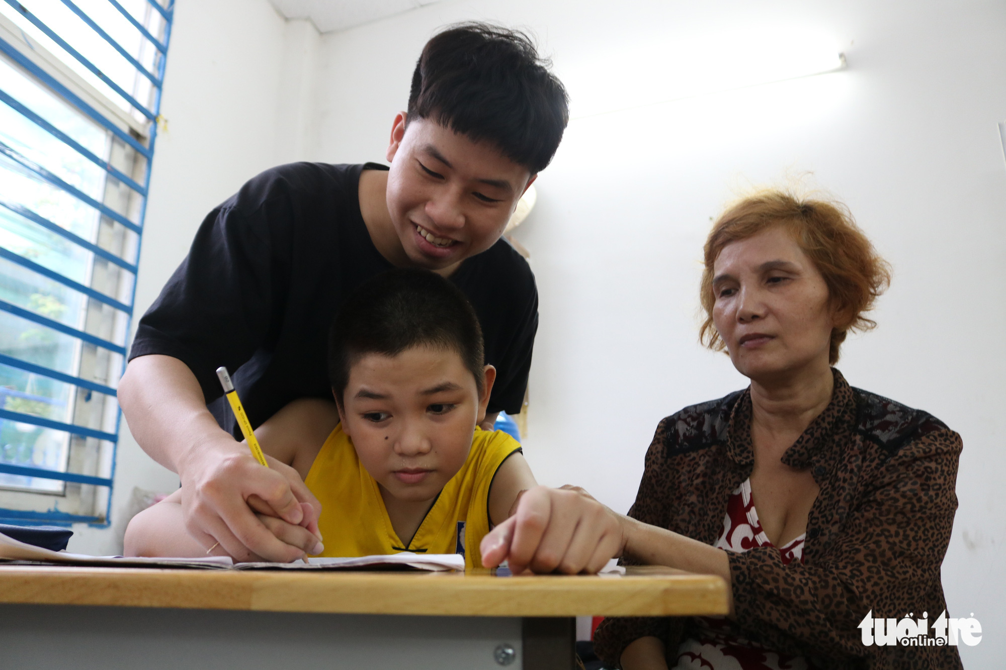 Nguyen Thi Xuan Thu (right) sits with her disabled child (left, sitting) as he is taught by Phan Trung Hai at a special class for underprivileged children in Ho Chi Minh City, Vietnam. Photo: Ngoc Phuong / Tuoi Tre