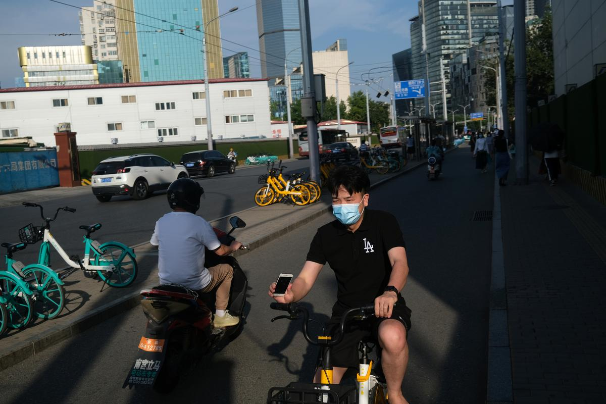 A man wearing a face mask rides a bicycle of the bike sharing service by Meituan, following the coronavirus disease (COVID-19) outbreak, in Beijing's central business area, China June 30, 2020. Photo: Reuters