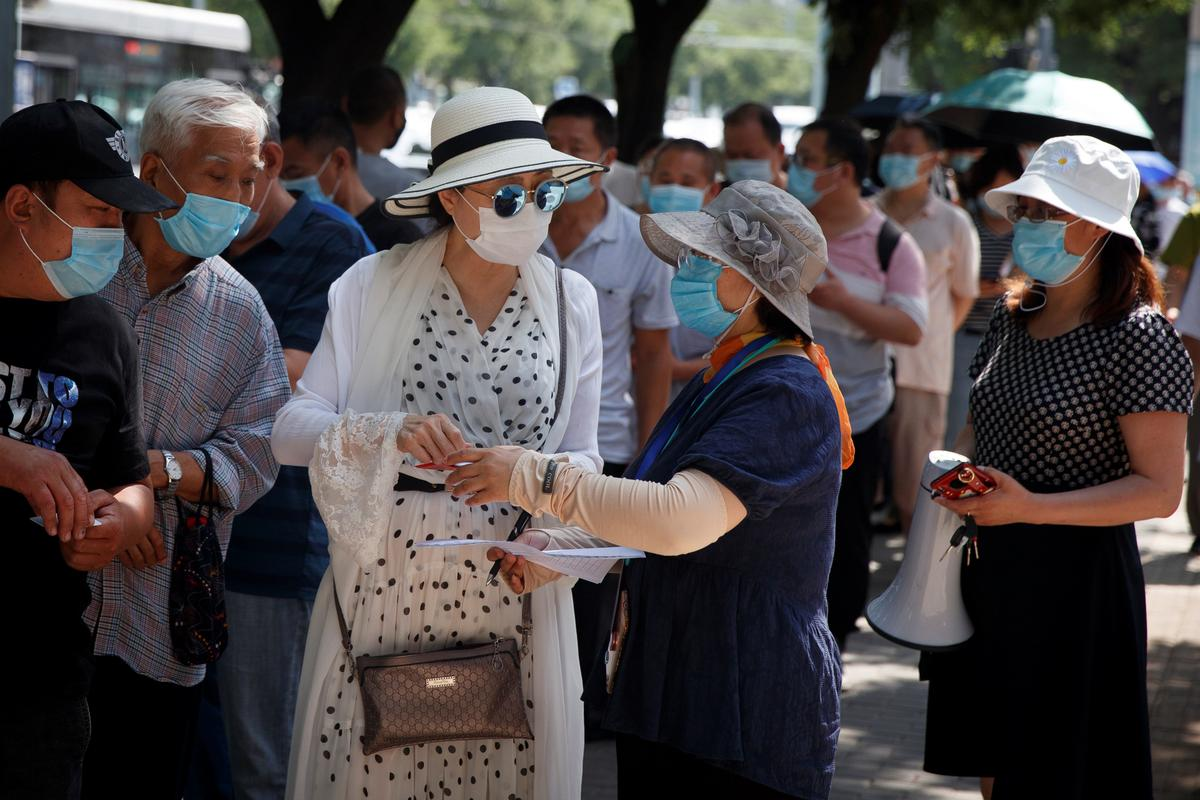 People line up to receive nucleic acid tests at a temporary testing site after a new outbreak of the coronavirus disease (COVID-19) in Beijing, China June 30, 2020. Photo: Reuters