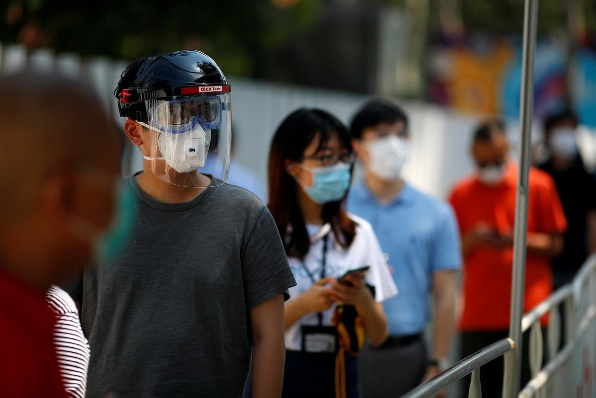 People line up to receive a nucleic acid test at a testing vehicle, following a new outbreak of the coronavirus disease (COVID-19) in Beijing, China, June 30, 2020. Photo: Reuters