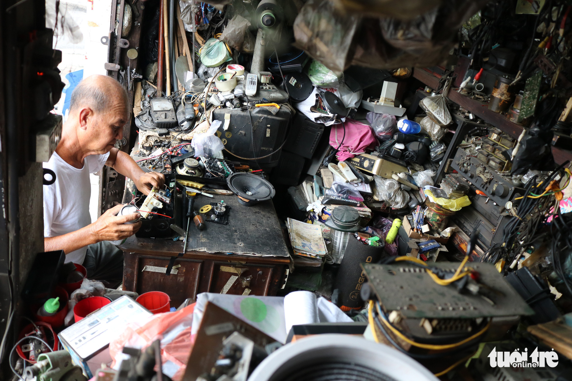 Tran Minh Tri repairs radio devices in the two-square-meter kiosk on Vo Van Ngan Street in Thu Duc District, Ho Chi Minh City. Photo: Hoang An / Tuoi Tre