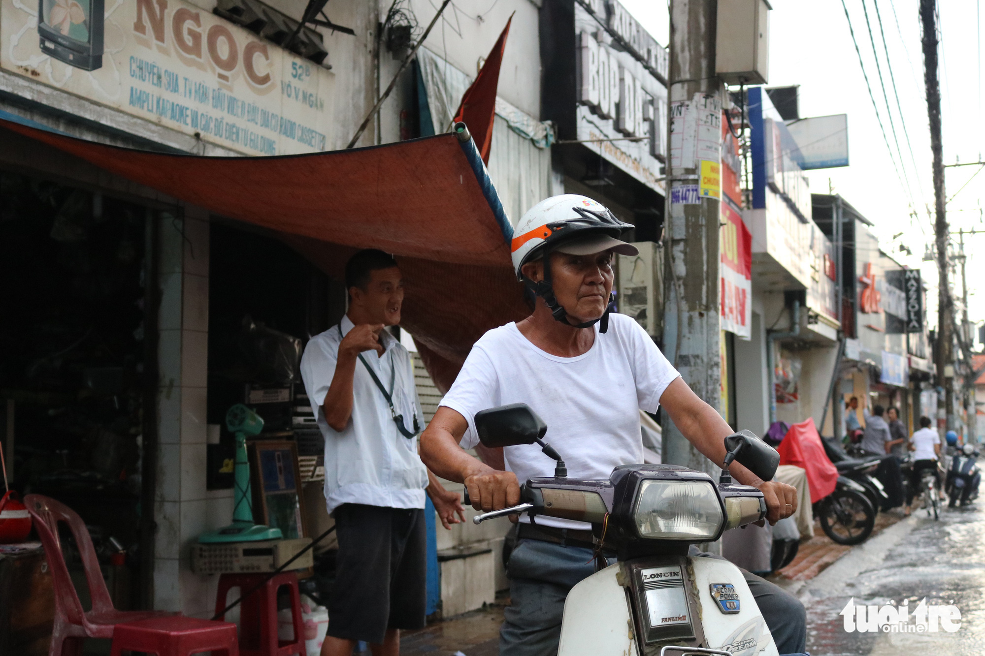 Tran Minh Tri (right) prepares for a motorbike taxi gig, leaving his son Anh Tu taking care of the repair shop on Vo Van Ngan Street in Thu Duc District, Ho Chi Minh City. Photo: Hoang An / Tuoi Tre
