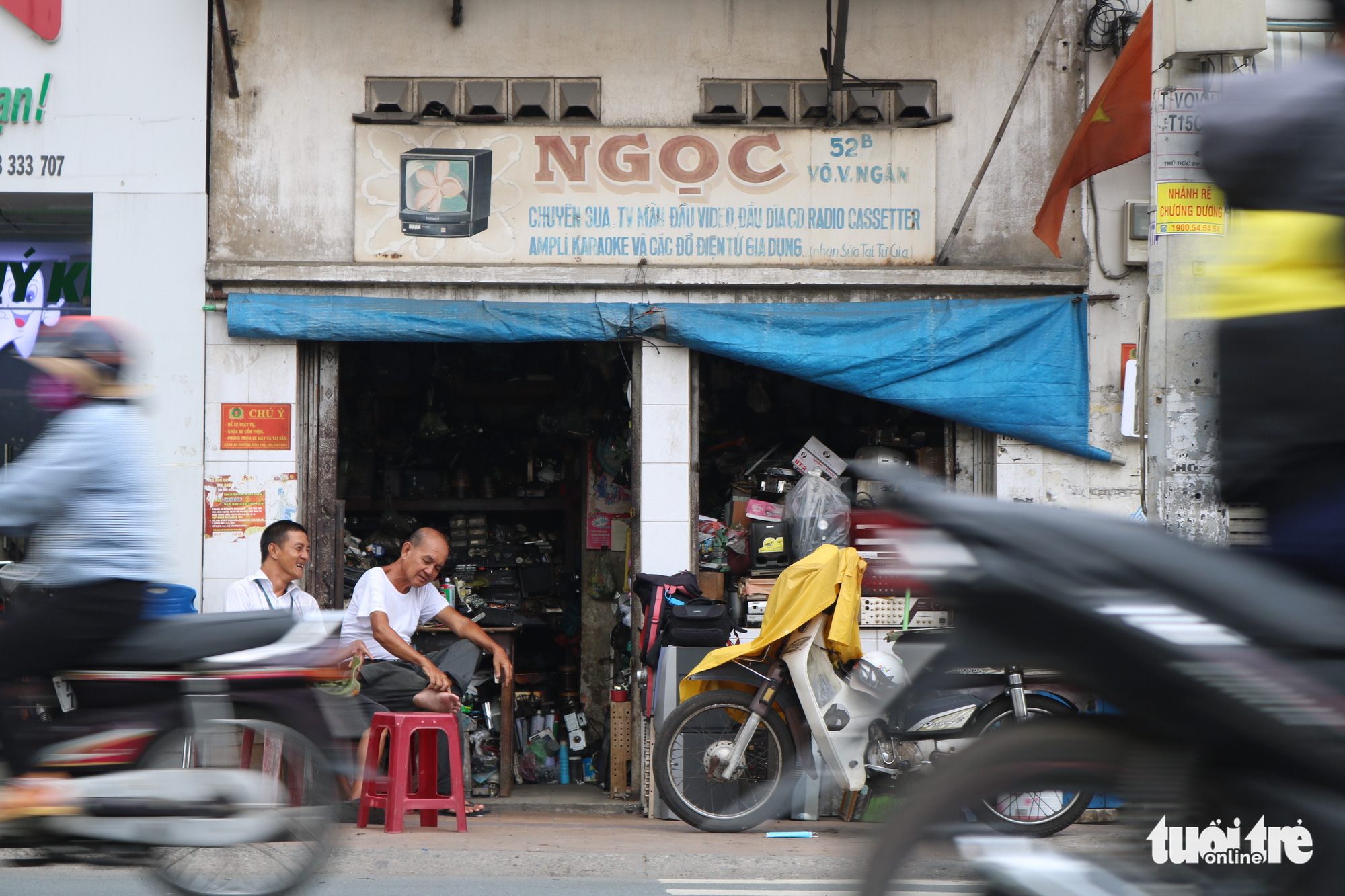 Tran Minh Tri (right) and his son Anh Tu sit in front of their radio repair shop on Vo Van Ngan Street in Thu Duc District, Ho Chi Minh City. Photo: Hoang An / Tuoi Tre