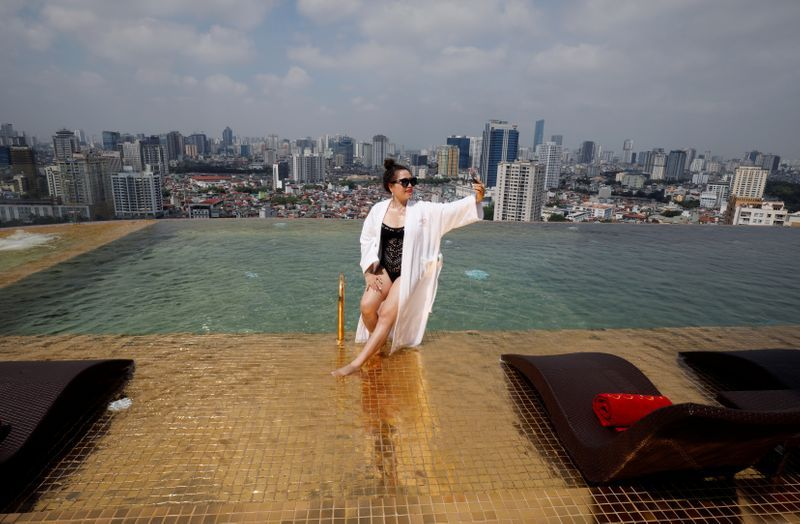 A woman poses for a photo at the gold plated infinity pool of the newly-inaugurated Dolce Hanoi Golden Lake luxury hotel, after the government eased nationwide social distancing following the global outbreak of the coronavirus disease (COVID-19), in Hanoi, Vietnam. Photo: Reuters