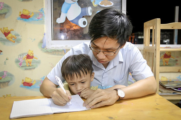 Danh Tuan Anh teaches one of his young students how to write in his tuition-free classes held in District 7, Ho Chi Minh City, Vietnam. Photo: Dieu Qui / Tuoi Tre