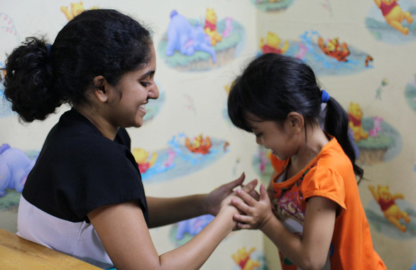 A volunteer teaches a young girl life skills in Danh Tuan Anh's tuition-free classes held in District 7, Ho Chi Minh City, Vietnam. Photo: Dieu Qui / Tuoi Tre