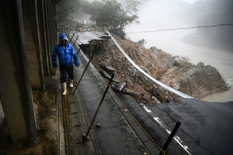 A person walks by a collapsed road caused by heavy rain in Kuma, Kumamoto prefecture, Japan, July 7, 2020. Photo: AFP