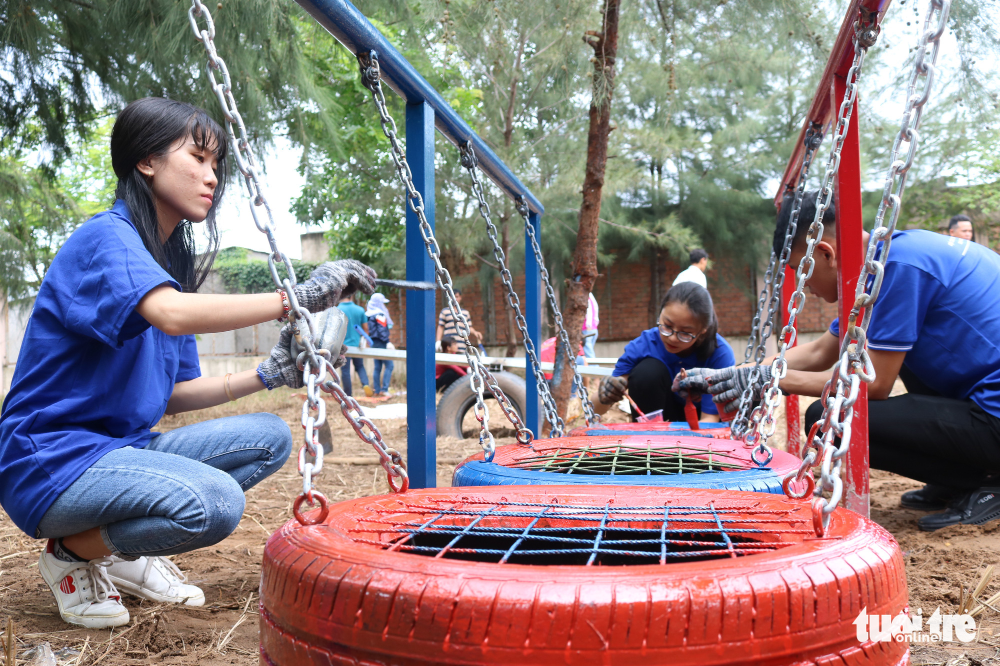 Volunteers apply the last coat of paint on a balance walk toy made from upcycled old tires in Nha Be District, Ho Chi Minh City, Vietnam. Photo: Hoang An / Tuoi Tre