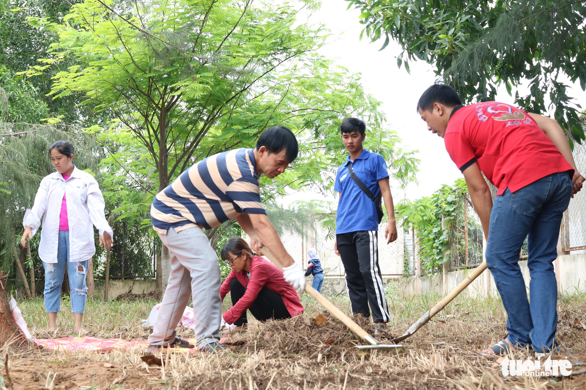Students from the University of Labour and Social Affairs clear the space intended to be used for a playground in Nha Be District, Ho Chi Minh City, Vietnam. Photo: Hoang An / Tuoi Tre