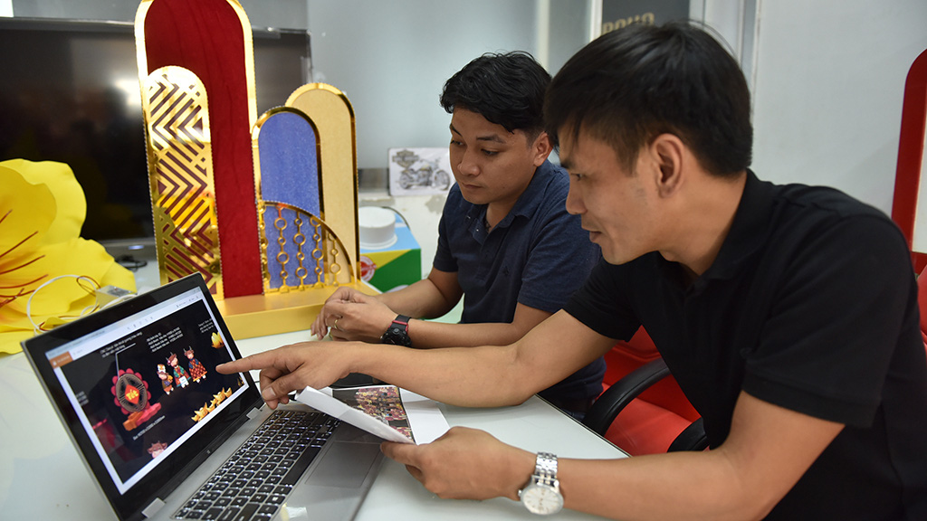 Two men check some mascot statue designs at a workshop in Binh Chanh District, Ho Chi Minh City. Photo: Ngoc Phuong / Tuoi Tre