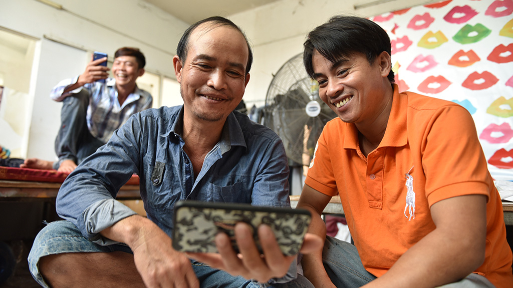 Seasonal workers talk with their family members via video calls at a workshop in Binh Chanh District, Ho Chi Minh City. Photo: Ngoc Phuong / Tuoi Tre