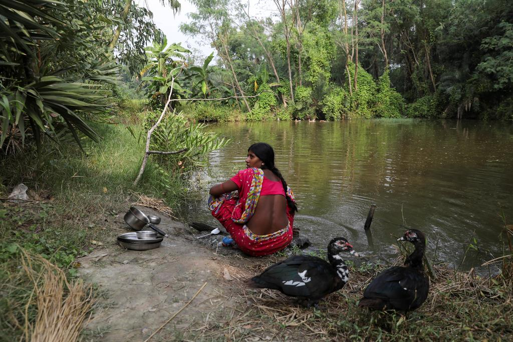 Ashtami Mondal, 30, whose 31-year-old husband Haripada, died in a tiger attack when he went fishing on the rivers encircling Kumirmari during a nationwide lockdown to prevent the spread of the coronavirus disease (COVID-19), cleans utensils in a pond next to her home on the island of Kumirmari in the Sundarbans, India, November 19, 2020. Photo: Reuters
