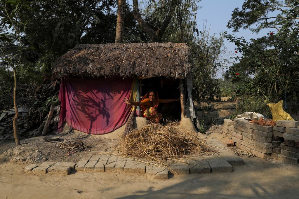 Namita Mondal, 32, whose husband died due to a tiger attack, gestures as she calls out to a family member from her home on the island of Satjelia in the Sundarbans, India, December 16, 2019. Photo: Reuters