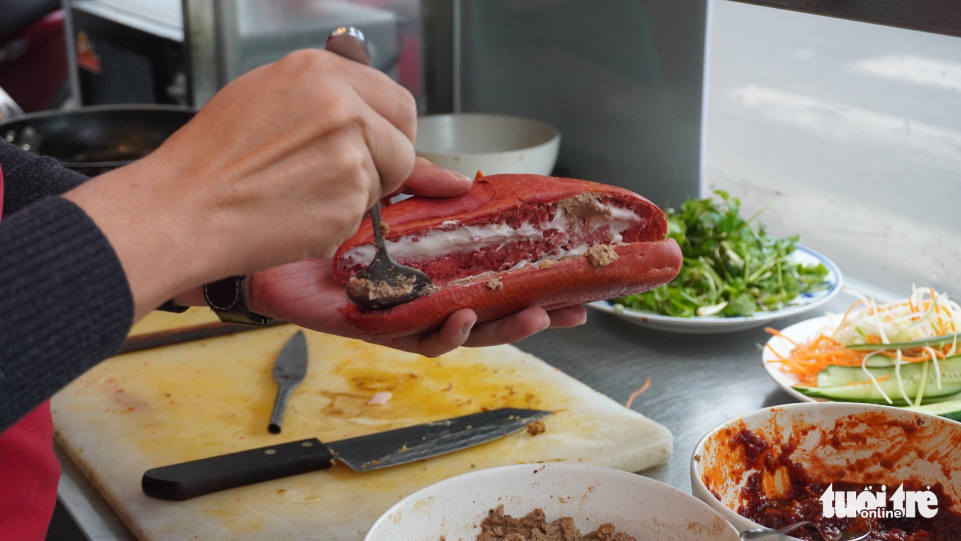 A banh mi is being stuffed with various fillings at Banh mi yeu nuoc in Da Nang City, Vietnam. Photo: Doan Nhan / Tuoi Tre
