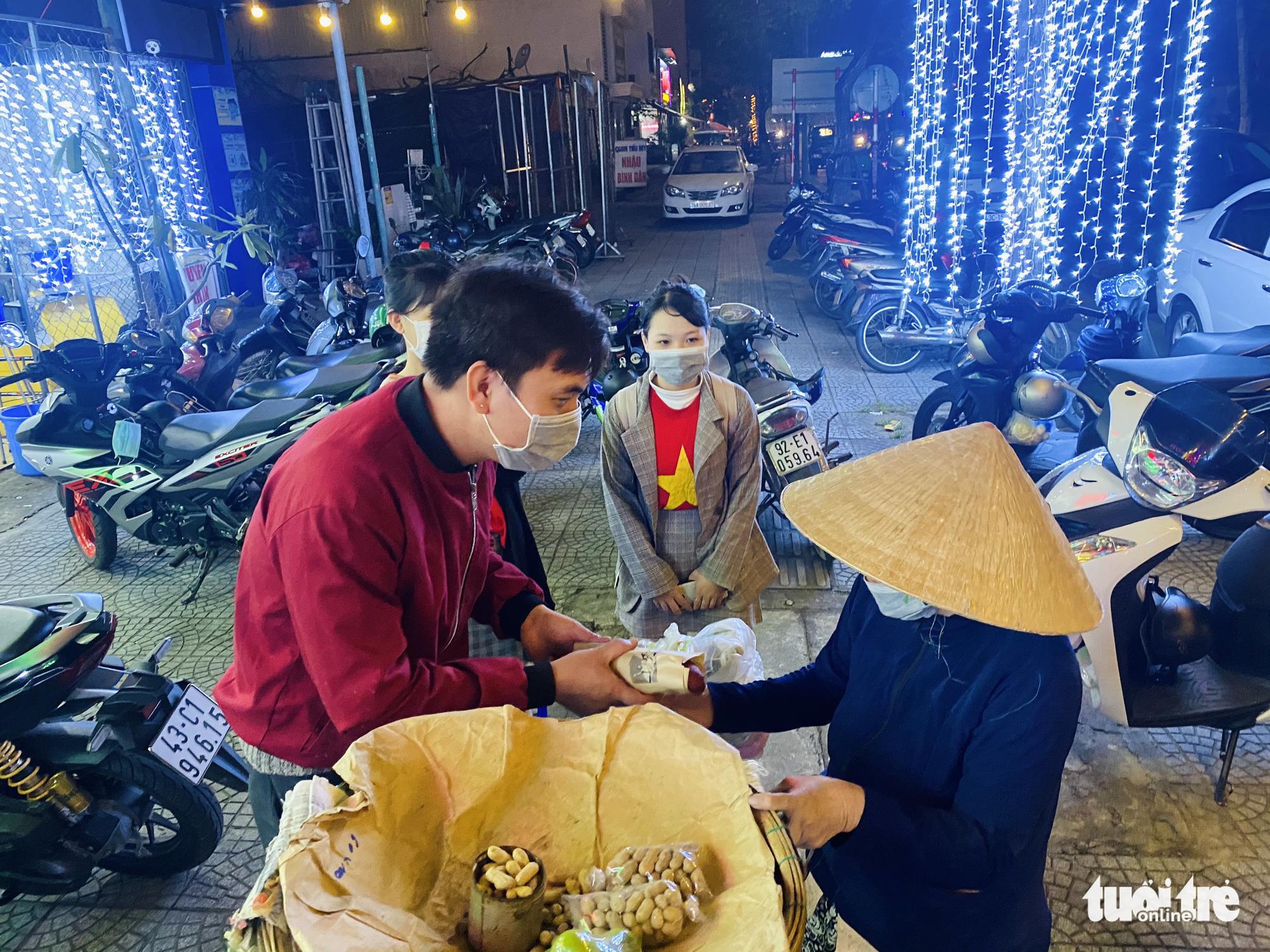 Young people give free banh mi to a woman in Da Nang City, Vietnam. Photo: Doan Nhan / Tuoi Tre