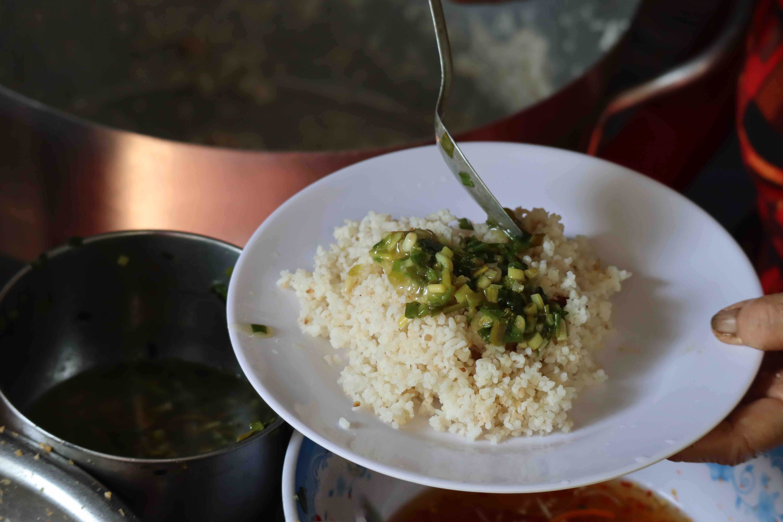 Diep Thi Ngoc Anh tops scallion oil on the broken rice at Com Tam Chi Nam, Tan Canh Street, Tan Binh District, Ho Chi Minh City. Photo: Nam Vuong / Tuoi Tre